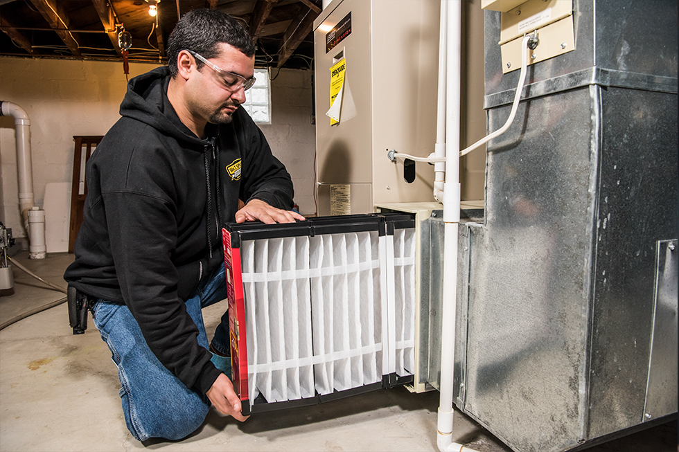 Technician changing furnace filter