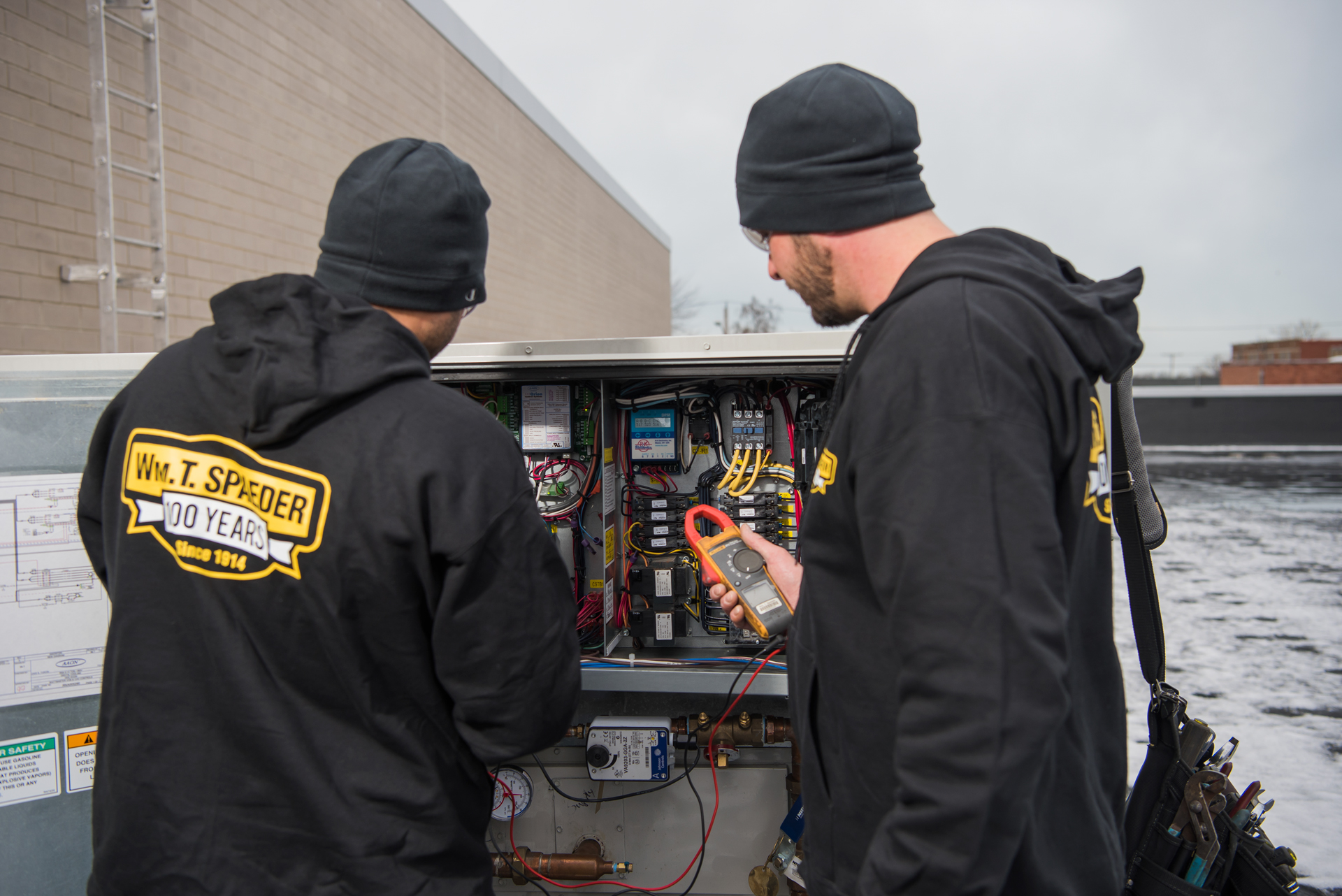 Spaeder technicians examining an air handling unit as part of an HVAC inspection.